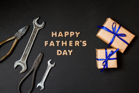 Greeting card to celebrate Fathers day. Two craft gifts with blue ribbons with tools on paper black background. Top view.
