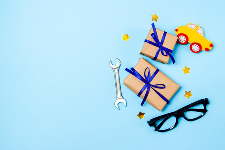 Father's day concept card with man's work tool on blue background and gifts boxes wrapped in kraft paper and tied with blue bow. Top view