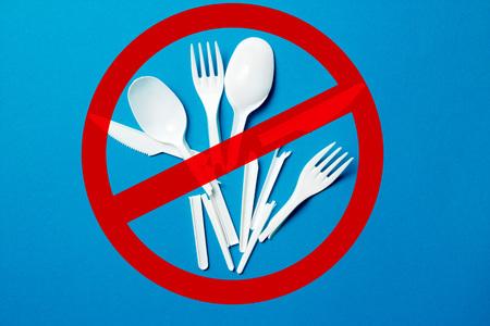 Coltelli di plastica monouso bianchi, cucchiai, forchette su sfondo blu. Diciamo no alla plastica monouso. Ambientale, concetto di inquinamento