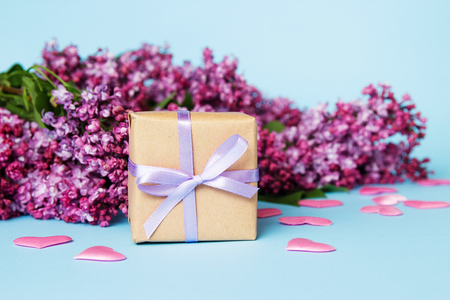 Frame of lilac flowers with gift box on a blue background. Mothers day.
