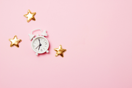 Retro alarm clock with party decoration on pink background. Copy space