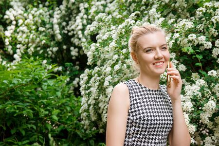 Young woman talking on a cell phone in a park near flowering bushes.