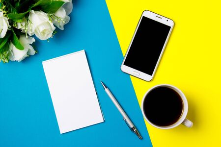 Smartphone, notepad and cup of coffee on a yellow and blue art background. Top view Stock fotó
