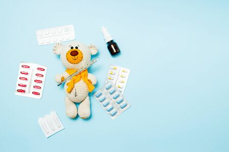 Children's knitted toy teddy bear with pills takes the temperature of a mercury glass thermometer on blue background. Child' disease concept