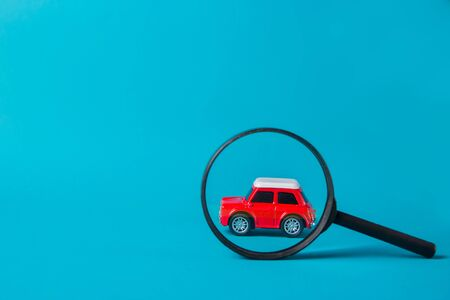 Red car peeked out with a magnifying glass on blue background. Technical inspection and machine search concept.