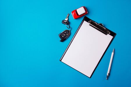 Paper blank with toy red car and keys on a blue background. Technical inspection or car credit concept. Top view and copy space. Stockfoto