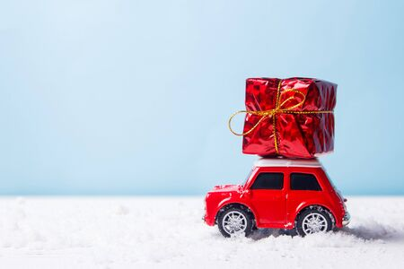 Miniature red car toy delivering gift box on blue background. Christmas greeting card concept Stock Photo
