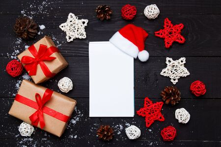 Weihnachtskomposition. Weihnachtsgeschenke und Notizblock mit Dekor auf schwarzem Holzhintergrund. Ansicht von oben, flach legen, Platz kopieren