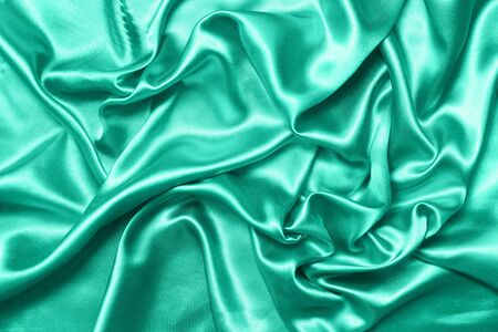 Close up of ripples on silk fabric. Satin textile background. Green color. Top view. Color of the year 2020.