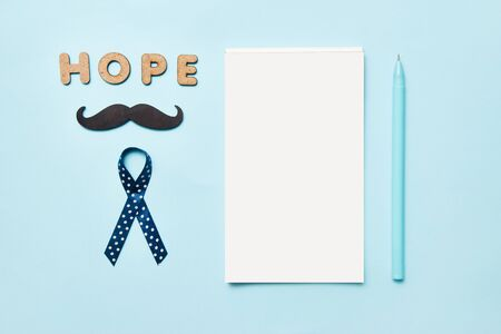 Blue ribbons with mustache, word hope and notepad with pen . Prostate Cancer Awareness. Men health awareness. Movember concept. Stock Photo
