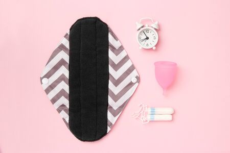 Reusable sanitary napkin, menstrual cup and tampons on a pink pastel background. Woman period concept. Eco friendly and alternative product for period . Flat lay, top view