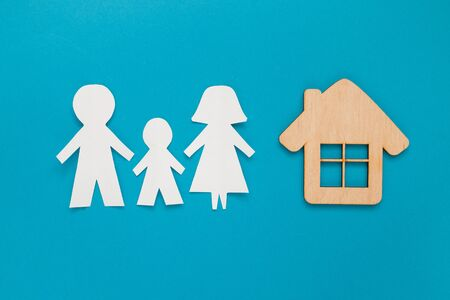 Family cut out paper with mini wood house model on blue background. Top view, flat lay.