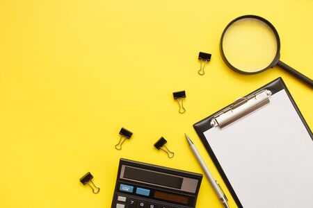 Search or choose a job. Career concept. Office supplies, blank and magnifier on a yellow background.