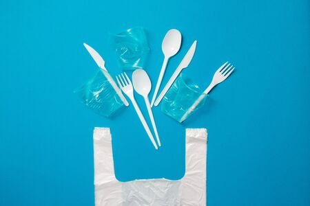 White single-use plastic knives, spoons, forks and bag on a blue background. Say no to single use plastic. Environmental, pollution concept Archivio Fotografico