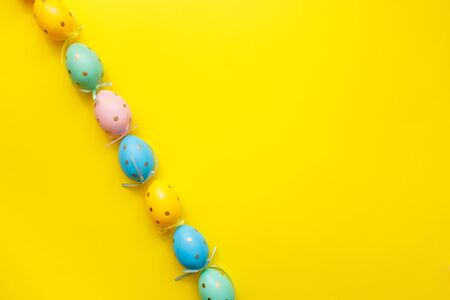 Easter colored eggs border on yellow background. Happy Easter greeting card minimal concept. Top view, flat lay, copy space