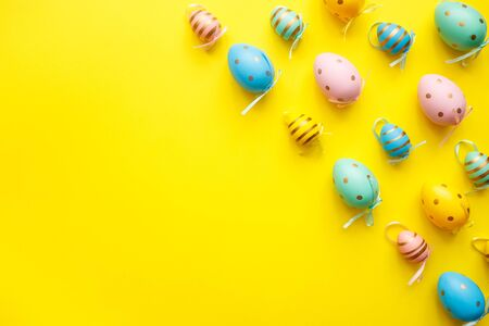 Easter colored eggs on yellow background. Happy Easter greeting card minimal concept. Top view, flat lay.