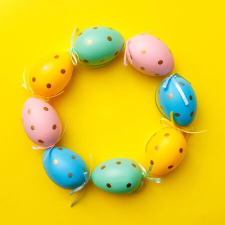 Easter colored eggs on yellow background. Happy Easter greeting card minimal concept. Top view, flat lay, copy space. 版權商用圖片