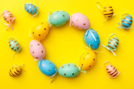 Easter colored eggs on yellow background. Happy Easter greeting card minimal concept. Top view, flat lay, copy space