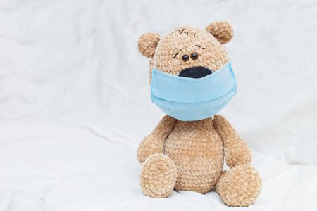 Cute teddy bear with face mask on his mouth on white background