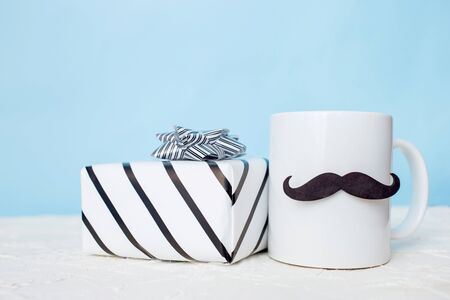 Greeting card fathers day holiday concept. White cup with mustache and gift box on blue pastel background