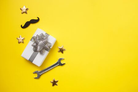 Father's day concept card with man's work tool on yellow background and gift box and mustache. Top view, flat lay, copy space