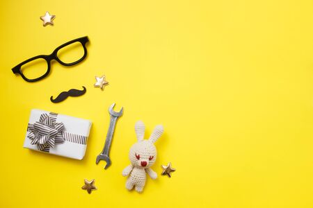 Father's day concept card with man's work tool on yellow background and gift box, mustache and glasses. Top view, flat lay, copy space Stok Fotoğraf