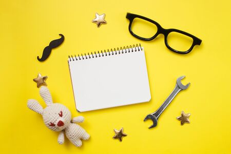 Father's day concept card with man's work tool on yellow background and gift box, mustache,glasses and notepad. Top view, flat lay, copy space