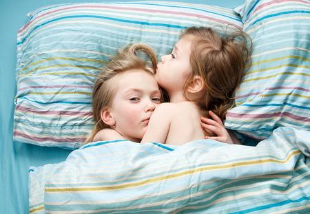 bedsheets: Two sisters sweet sleep holding hands Stock Photo