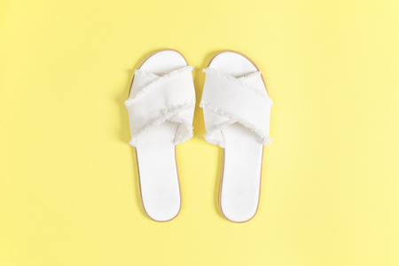 Womens white fabric sandals on a yellow background