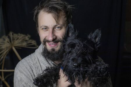smiling man hugging his dog, a Scottish Terrier. Four-legged friend and his master