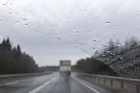 the view from the window of a moving car in rainy weather. Defocused track and cars. Speed in poor visibility conditions