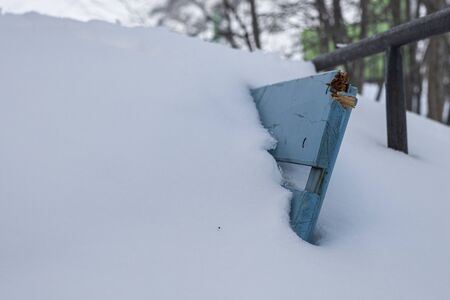the angle of the bench sticking out of the snow. The harsh winter in the far North Banco de Imagens