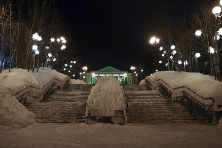 Snowy urban ladder with lights. Night city landscape