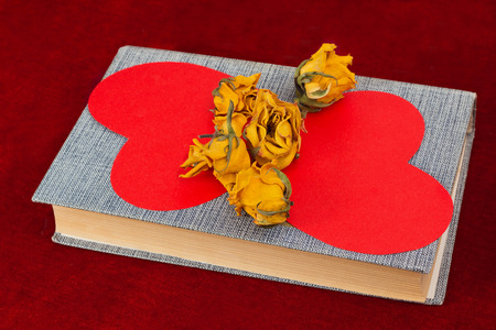 st  valentin: Five dried yellow roses and two red paper hearts lying on the book