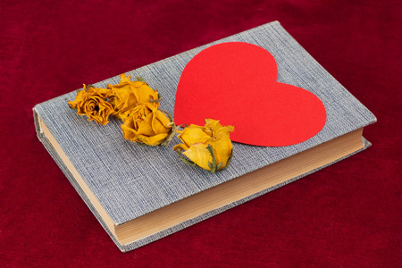 st  valentin: Four dried yellow roses and red paper heart lying on the book