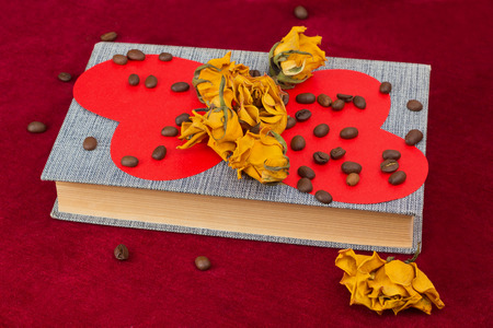st  valentin: Five dried yellow roses and two red paper hearts lying on the book with coffee beans