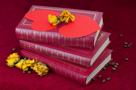 st  valentin: Two red paper hearts lying on the three red books with several dried yellow roses and coffee beans