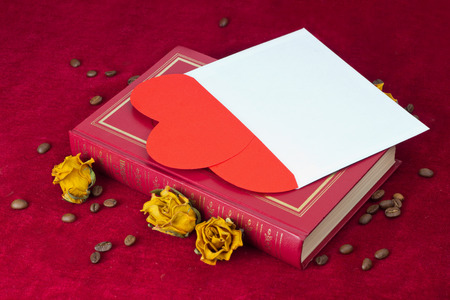 st  valentin: Two red paper hearts in the envelope lying on the red book with several dried yellow roses and coffee beans