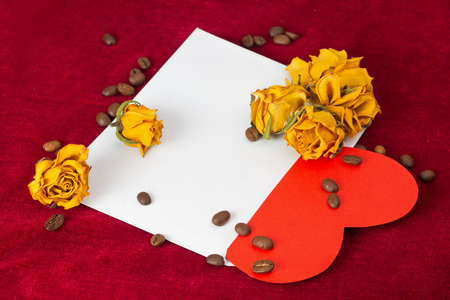 st  valentin: Red paper heart in the envelope with several dried yellow roses and coffee beans