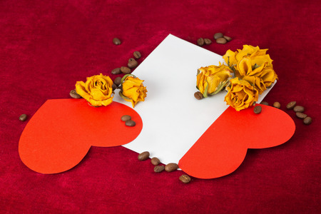 st valentin: Two red paper hearts in the envelope with several dried yellow roses and coffee beans