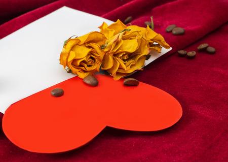 rosas amarillas: Corazón de papel rojo tirado en el sobre con dos rosas amarillas secos y los granos de café Foto de archivo