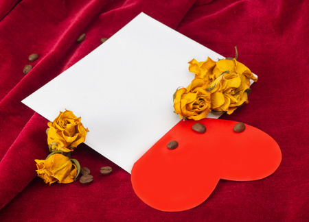 st  valentin: Red paper heart lying on the envelope with two dried yellow roses and coffee beans Stock Photo