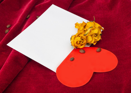 st  valentin: Red paper heart lying in the envelope with two dried yellow roses and coffee beans Stock Photo