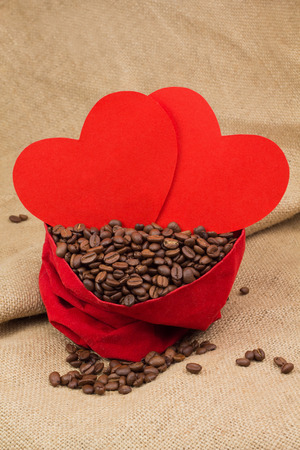 st  valentin: Coffee beans in red velvet sac with two red paper hearts Stock Photo
