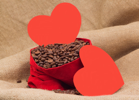 st  valentin: Two red paper hearts with coffee beans in red velvet sac Stock Photo