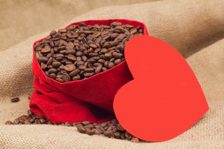 st  valentin: Red paper heart next to velvet red sac with coffee beans