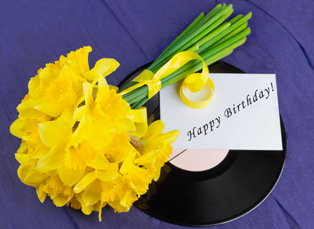 Bucket of narcissus flowers with yellow ribbon, an envelope with text on purple background and vinyl record photo