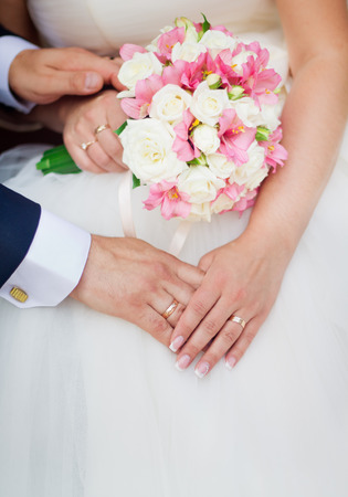 Wedding couple holding hands with a bouquet of flowers photo