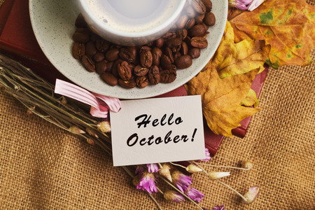 october: Tag with the words hello october and the cup of coffee lying on the books with dry yellow maple leaves and everlasting flowers on sackcloth background Stock Photo