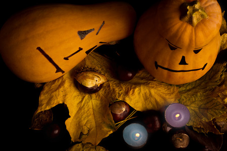 jacks: Halloween pumpkin head jacks with maple leaves, chestnuts and candles on black background